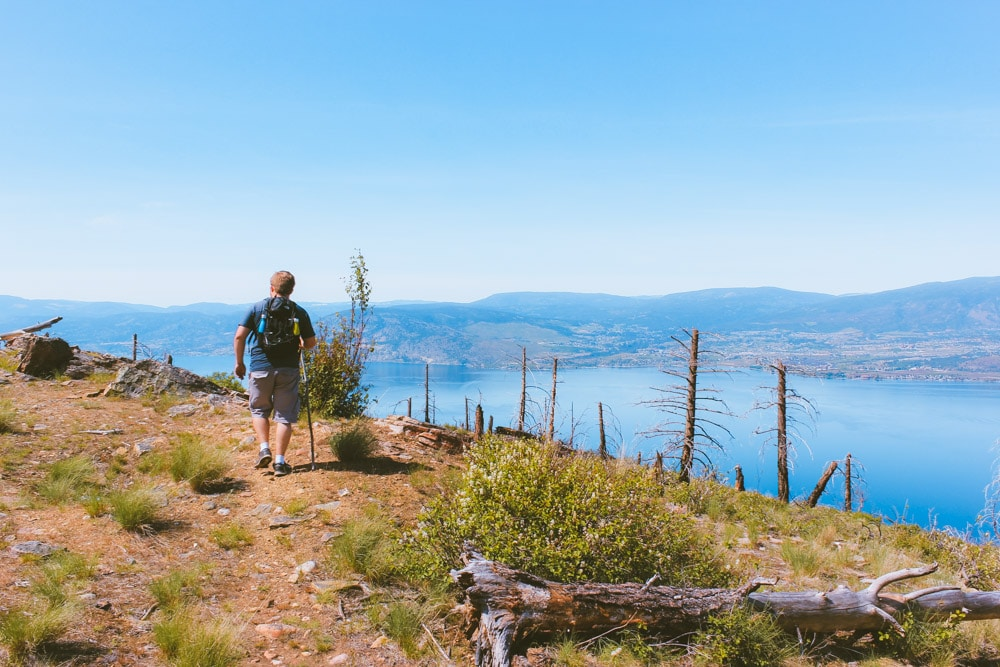 Jacob from Explore the Map hikes at on the trail at Johns Family Park with a view of Okanagan Lake in the background.