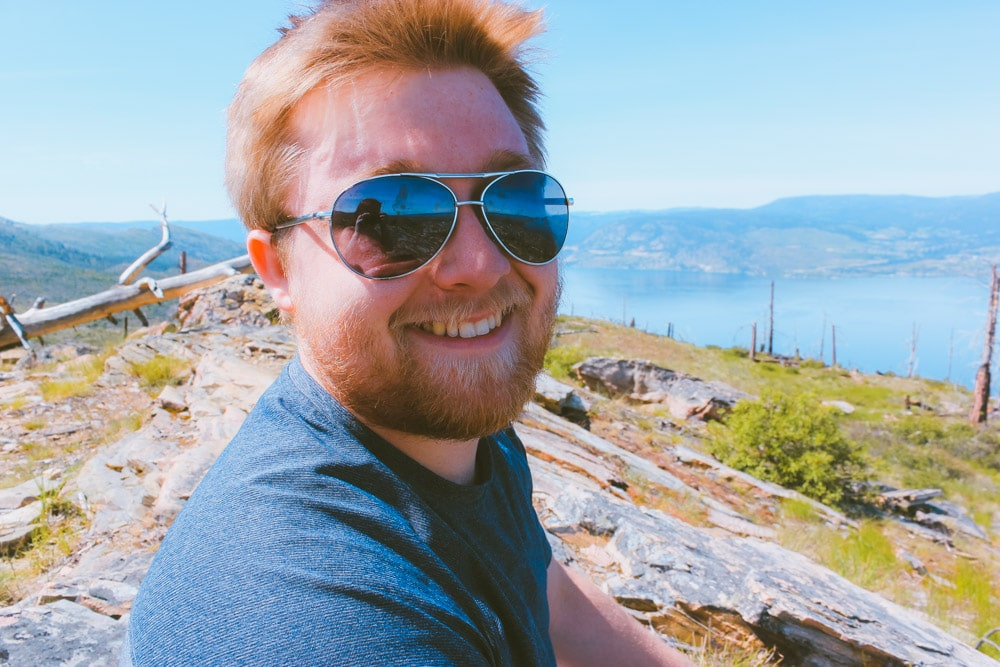 Portrait of a smiling man at the summit of the Crags at Johns Family Regional Park in Kelowna with views of Okanagan Lake in the background