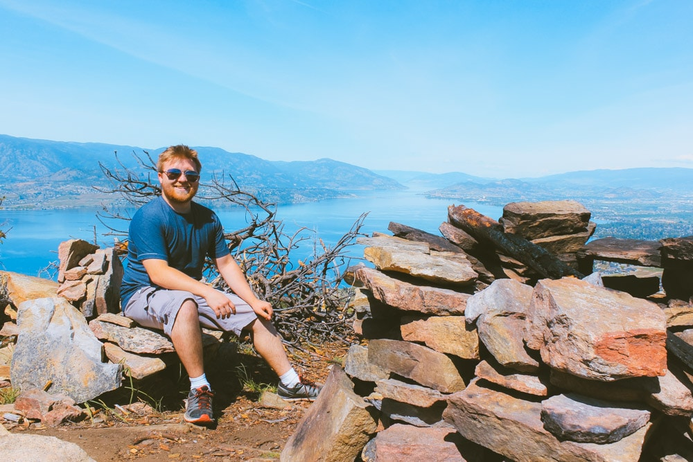 Jacob from Explore the Map sits in the stone chairs near the firepit at the summit of the Johns Family Park hike in Kelowna. Amazing viewpoint with views of Kelowna and Okanagan Lake.
