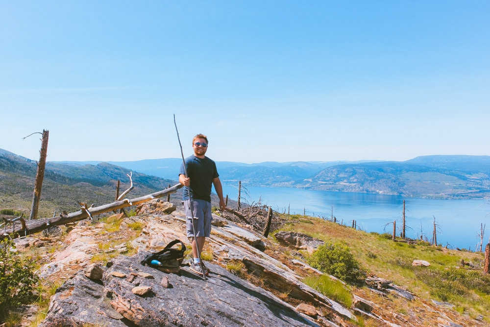 Man stands at the summit of Johns Family on a sunny day