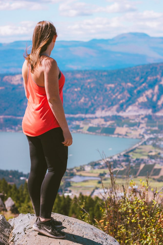 Woman with a red shirt stands on a rock at the Oyama Lookout with views of Wood Lake and Oyama in the background