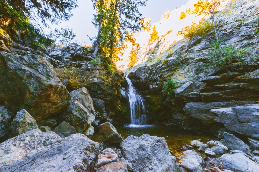 The lower waterfall at Crawford Falls in Kelowna. A gentle waterfall is nestled in a rocky canyon.