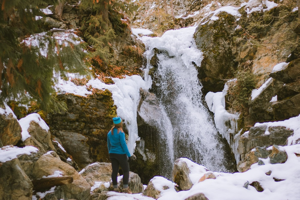 The frozen lower waterfall at Crawford/Canyon Falls in Kelowna. Woman stands in front of the waterfall.