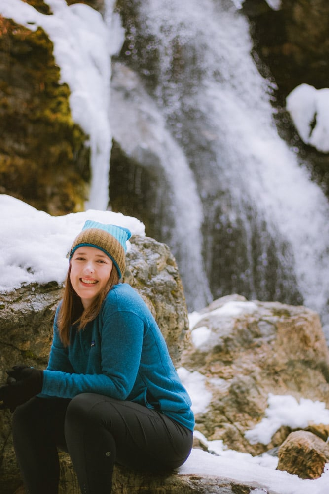 Woman sits in front of a frozen waterfall.