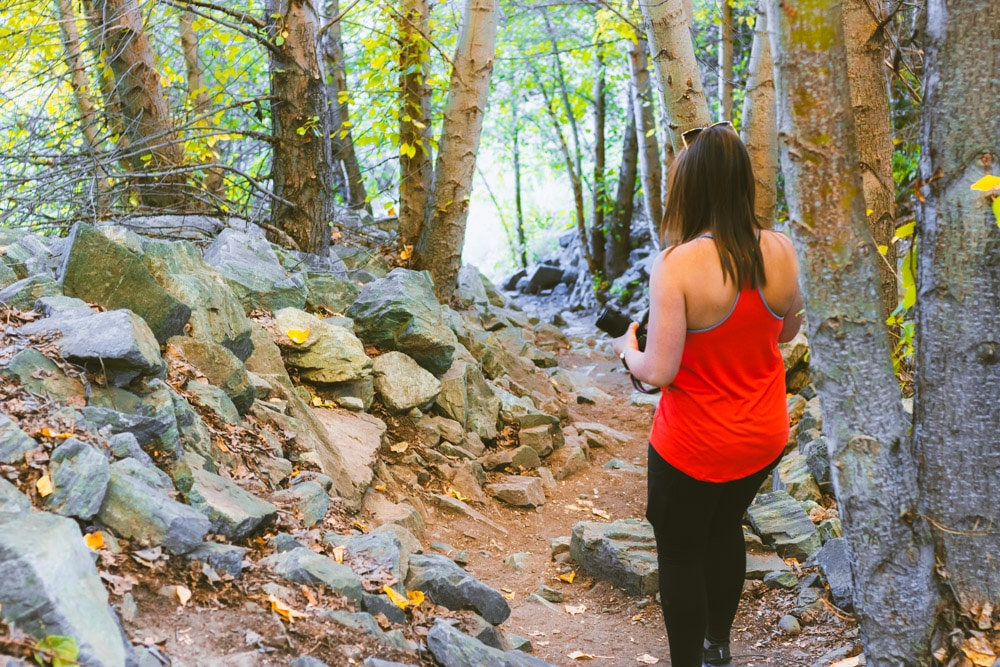 Woman hikes down a tunnel of trees.