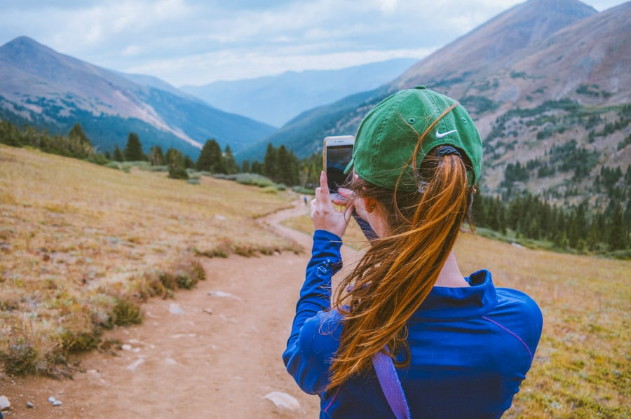 Woman hiker uses a hiking app to identify a mountain peak