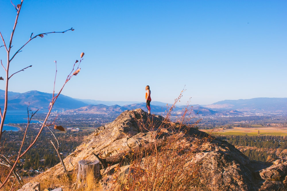 Woman in red stands on top of the main viewpoint at Kuipers Peak with views of Kelowna in the distance.