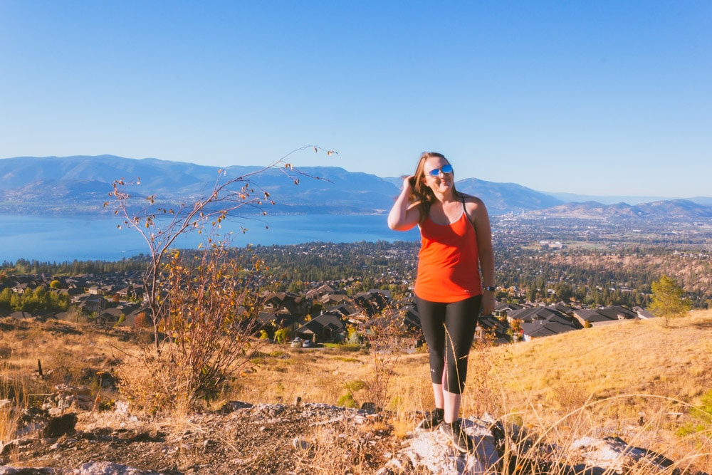 A women in red smiles for the camera at Kuipers Peak with a panoramic view of Kelowna and Okanagan Lake in the background.