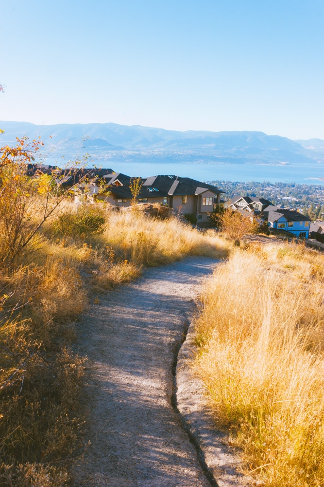 A gravel trail heads down the mountain towards fancy houses.