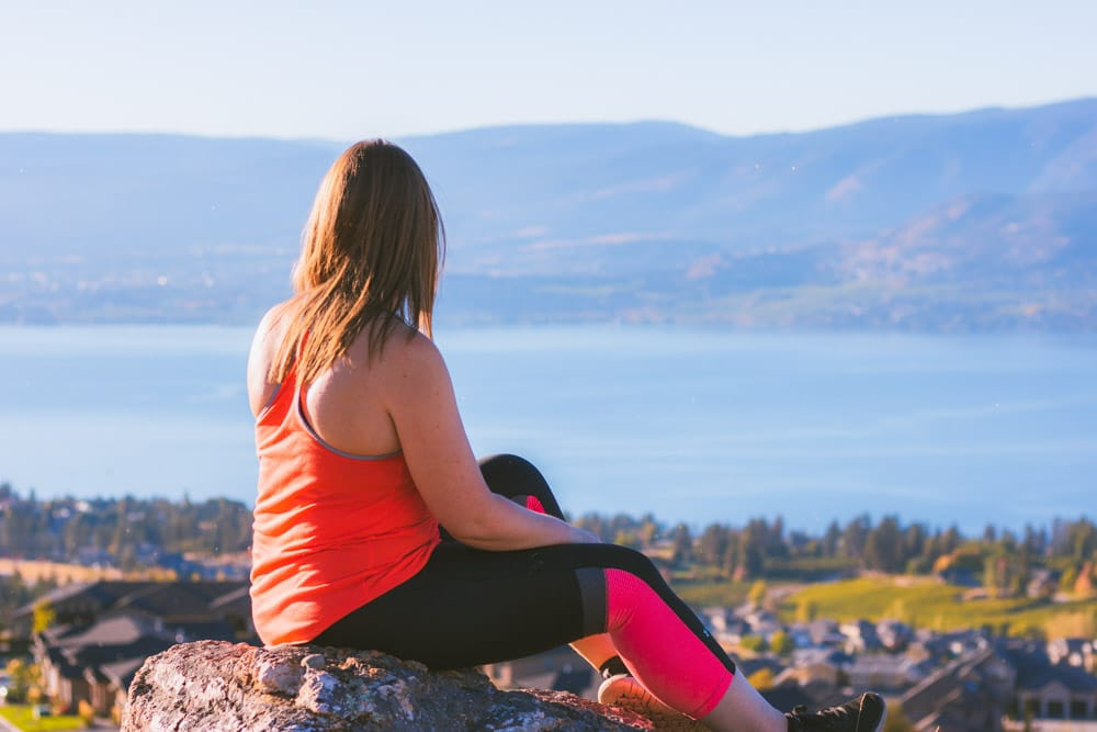 A women sits at a viewpoint at Kuipers Peak with Okanagan Lake in the background.