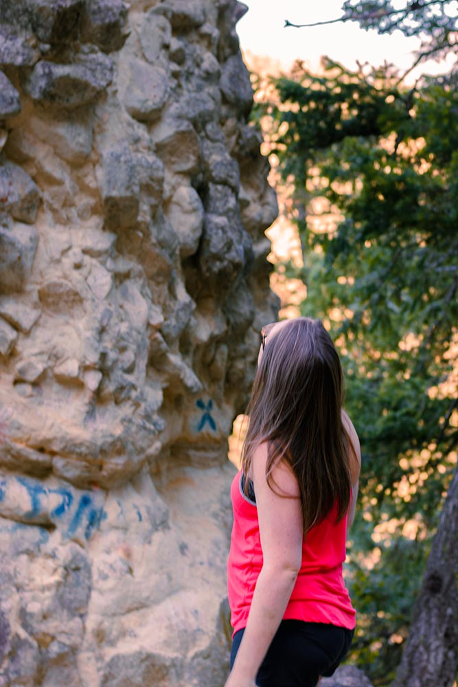Close-up of a woman in red standing at the base of a rocky column.