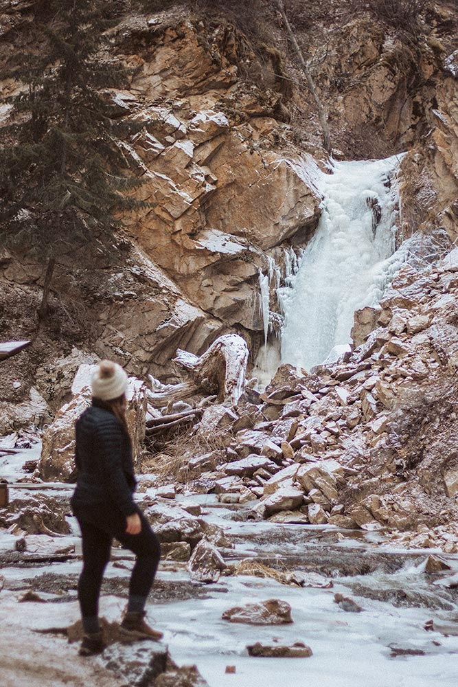 Women in hiking clothes stands in front of the frozen Hardy Falls in the winter