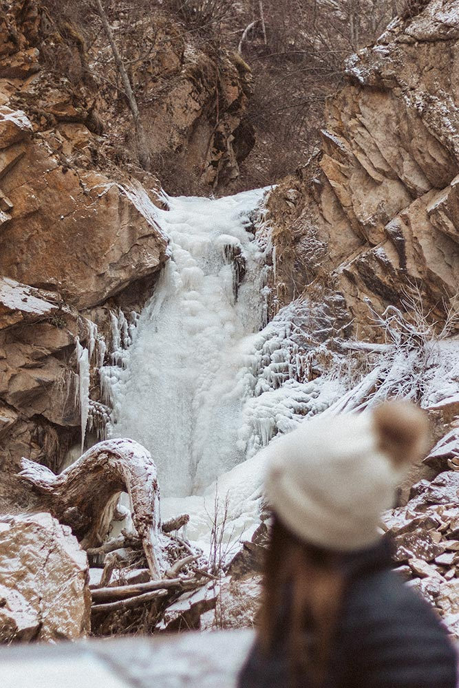 Woman looks at the frozen Hardy Falls