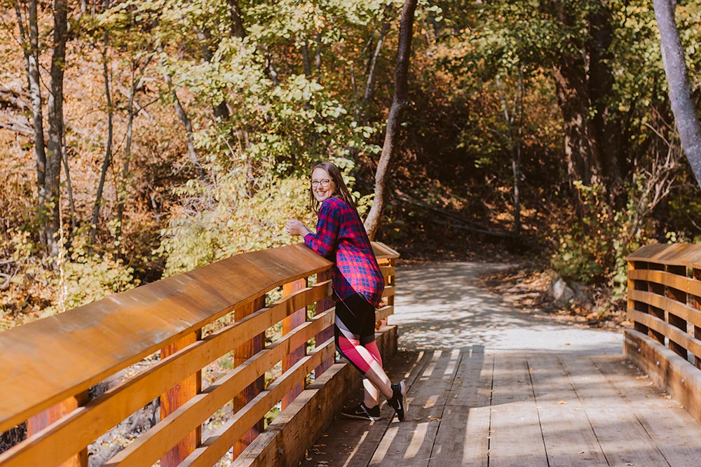 Woman stands on a bridge on the Hardy Falls trail in Peachland