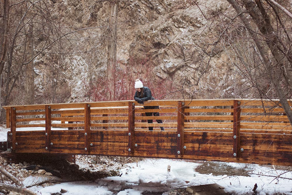 Woman looks over the edge of a bridge in the winter at Hardy Falls
