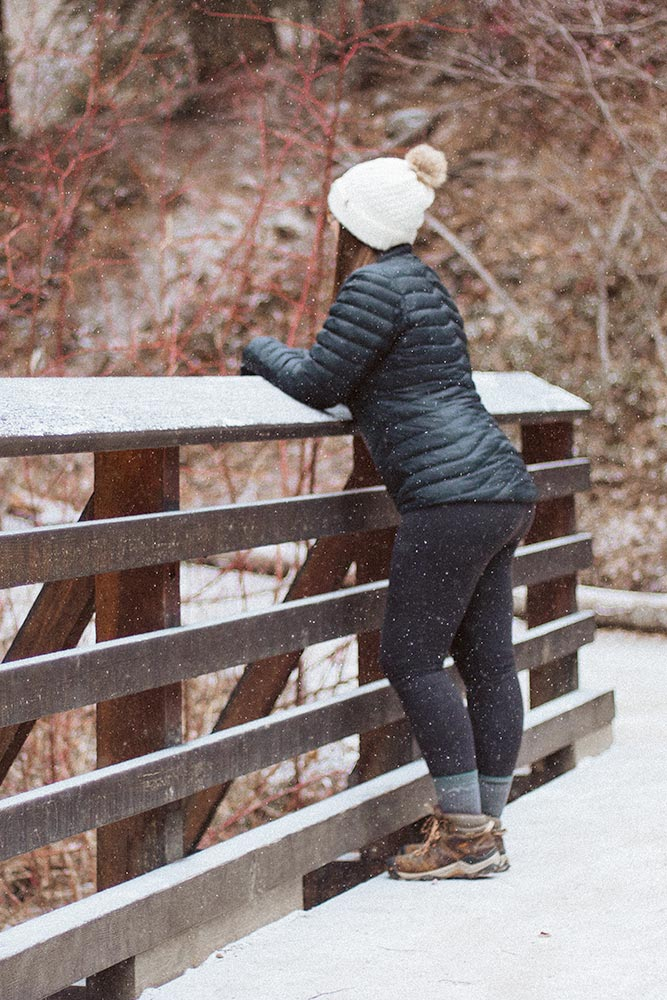 Woman stands on a bridge in the winter