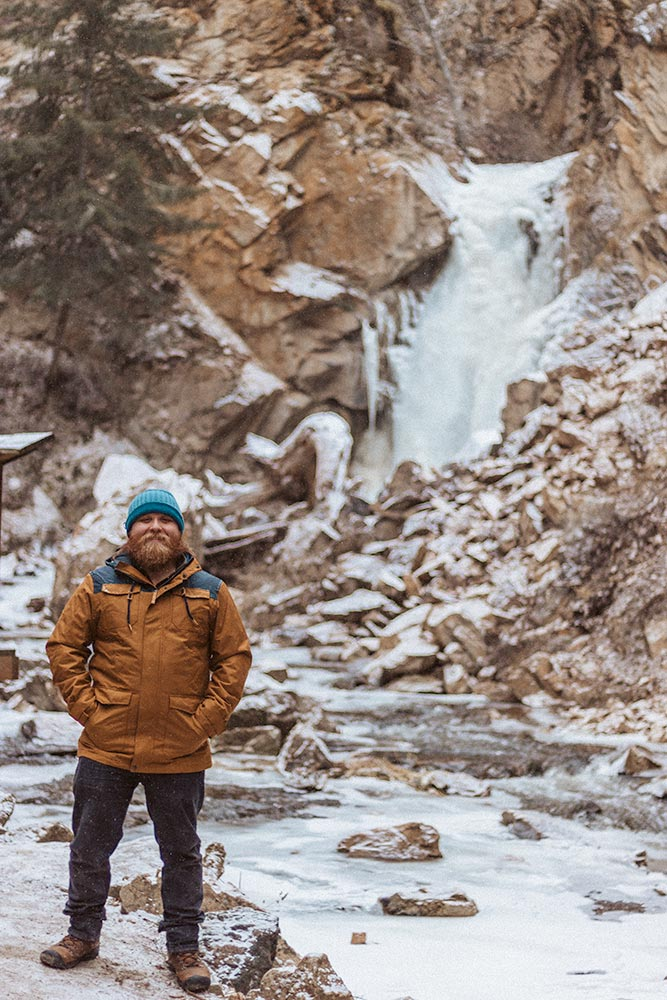 Man stands in front of the frozen Hardy Falls in Peachland