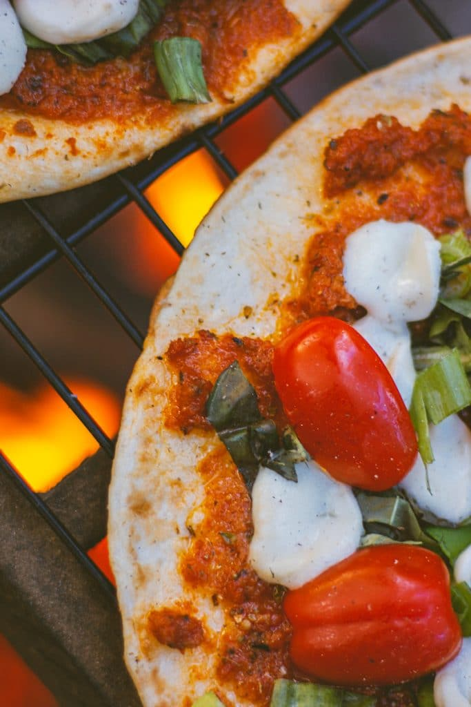 Closeup of a camping pizza on top of a campfire