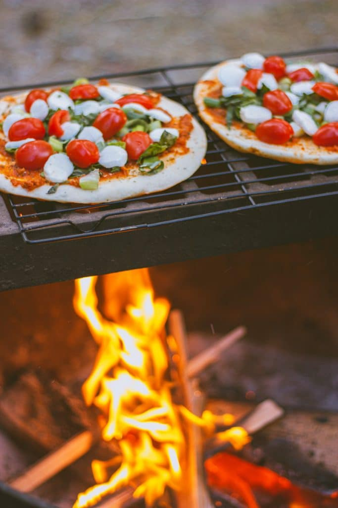 Pizza warms on top of a campfire