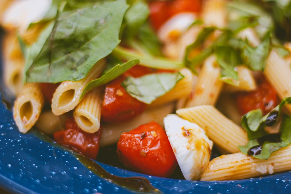 Closeup of pasta, bocconcini, and cherry tomatoes for this Caprese Pasta Salad camping recipe