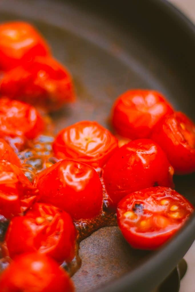 Closeup of cooking cherry tomatoes on a lightweight frying pan.
