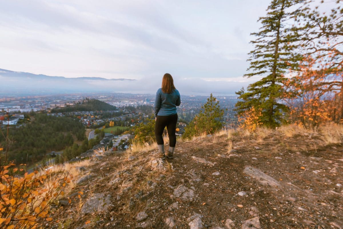 Woman in blue shirt stands at the Dilworth viewpoint and looks over Kelowna on a cloudy day.